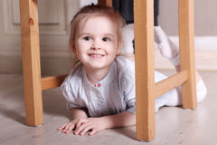 Little cute blond girl in striped shirt is smiling on floor unde Royalty Free Stock Images