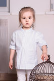 Little cute blond girl in striped shirt stands and extends hand Royalty Free Stock Images