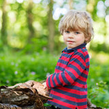 Little cute blond kid boy having fun in summer forest. Royalty Free Stock Photography