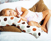 Little cute blonde girl playing at home with pillows Stock Image