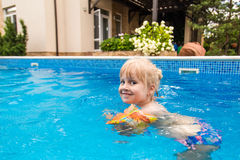 Little cute blonde girl swimming in a pool , wearing inflatable sleeves. She is smiling and happy Royalty Free Stock Photos