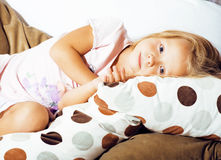 Little cute blonde norwegian girl playing on sofa with pillows, crazy home alone, lifestyle people concept Royalty Free Stock Image