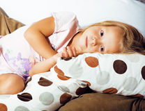 Little cute blonde norwegian girl playing on sofa with pillows, Stock Images