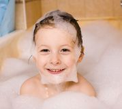 Little cute boy in bathroom with bubbles Stock Images