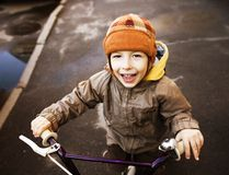 Little cute boy on bicycle smiling close up in hat Stock Images