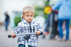 Little cute boy on the bike in city. Cute little boy rides his bike outdoors in city street royalty free stock image