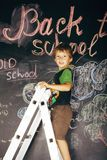 Little cute boy at blackboard in classroom, back Stock Photos