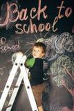 Little cute boy at blackboard in classroom, back Stock Images