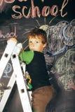 Little cute boy at blackboard in classroom, back Royalty Free Stock Image