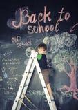Little cute boy at blackboard in classroom Stock Photo