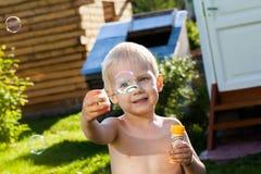 Little cute boy blow bubbles on summer grass smile fun Royalty Free Stock Photos