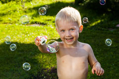 Little cute boy blow bubbles on summer grass smile Stock Photos
