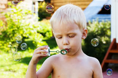 Little cute boy blow bubbles on summer grass smile Royalty Free Stock Images