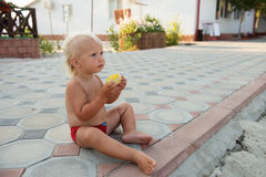 Little cute boy with blue eyes eating corn. Royalty Free Stock Images
