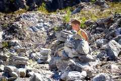 Little cute boy building tower of stones Royalty Free Stock Photo
