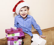 Little cute boy with Christmas gifts at home. close up emotional face on boxes in santas red hat Stock Photos