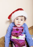 Little cute boy with Christmas gifts at home. close up emotional face on boxes in santas red hat Stock Photography