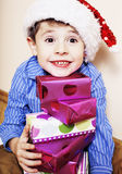Little cute boy with Christmas gifts at home. close up emotional. Face on boxes in santas red hat smiling Stock Images