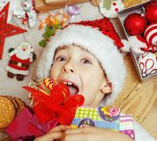 Little cute boy with Christmas gifts at home. close up emotional happy smiling in mess with toys, lifestyle holiday Royalty Free Stock Photo
