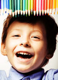 Little cute boy with color pencils close up smiling, education f stock image