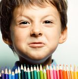 Little cute boy with color pencils close up smiling, education face colored stock photo