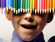 Little cute boy with color pencils close up smiling, education face colored Royalty Free Stock Images