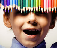 Little cute boy with color pencils close up smiling, education face colored Stock Photos