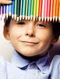 Little cute boy with color pencils close up smiling, education face colored Stock Image