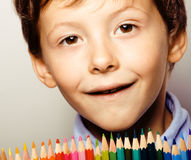 Little cute boy with color pencils close up smiling, education face colored Stock Images