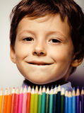 Little cute boy with color pencils close up smiling, education face colored Stock Photography