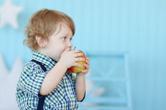 Little cute boy with curly hair bites red apple Royalty Free Stock Photos