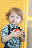 Little cute boy with curly hair holds apple Stock Images