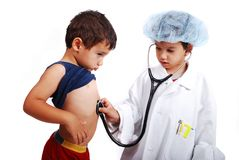 A little cute boy in doctor clothes is playing wit Royalty Free Stock Images