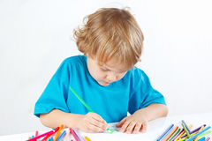 Little cute boy draws with color pencils on white background Stock Photography