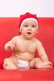 Little cute boy dressed in santa clause hood. Sitting on sofa Royalty Free Stock Image