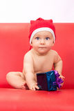 Little cute boy dressed in santa clause hood. Sitting on sofa with a gift Stock Photos