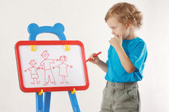 Little cute boy drew a family on a whiteboard Royalty Free Stock Photos