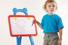 Little cute boy drew a sun on the whiteboard Royalty Free Stock Photos