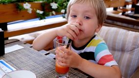 Little cute boy drinking carrot fresh juice in a cafe, close up stock video footage