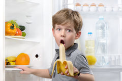 Little cute boy eating banana near open fridge Royalty Free Stock Photo