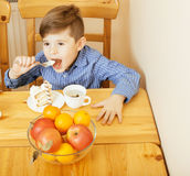 Little cute boy eating dessert on wooden kitchen. home interior. smiling adorable kid, healthy or unhealthy food concept Stock Images