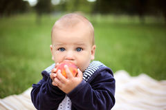 Little cute boy eating a peach in summer park Stock Photos