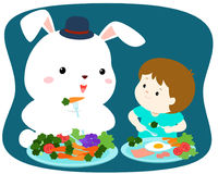 Little cute boy eating vegetable with white rabbit . Royalty Free Stock Images