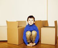 Little cute boy in empty room, move to new house. home alone among boxes close up kid smiling, lifestyle real people. Concept closeup stock photos