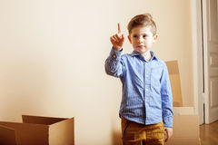 Little cute boy in empty room, remoove to new house. home alone emong boxes Royalty Free Stock Image