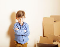 Little cute boy in empty room, remoove to new house. home alone emong boxes Stock Photo