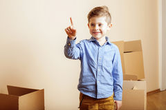 Little cute boy in empty room, remoove to new house. home alone emong boxes Royalty Free Stock Photos