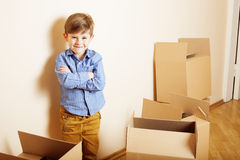 Little cute boy in empty room, remoove to new house. home alone emong boxes Stock Photos