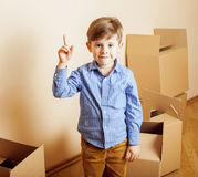Little cute boy in empty room, remoove to new house. home alone emong boxes Stock Images