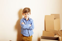 Little cute boy in empty room, remoove to new house. home alone emong boxes Royalty Free Stock Photo